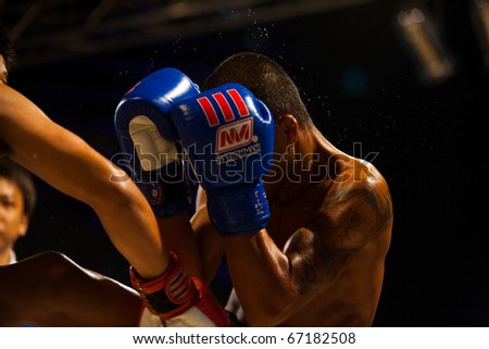 Bangkok, Thailand - October 12, 2010: Asian boxer with gloves up receiving punch to head sending sweat flying at outdoor amateur muay thai kickboxing match - stock photo