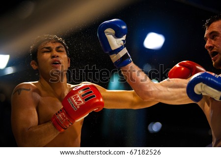 Bangkok, Thailand - October 12, 2010: Caucasian fighter landing uppercut to face of Thai Asian boxer, sweat flying during outdoor amateur muay thai kickboxing match