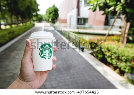Bangkok ,Thailand - OCTOBER 11, 2016 : Hand holding a cup of Starbucks hot beverage coffee while walking on the part in the park. Starbucks is the world's largest coffeehouse company