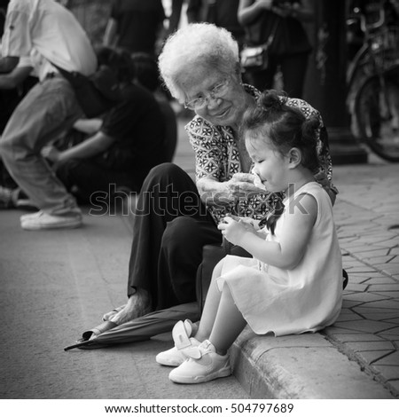 Bangkok, Thailand - October 18, 2016 : Old lady and little girl are sitting on the footpath in front of the Royal Grand Palace for the King Bhumibol Adulyadej funeral.
