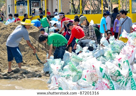 BANGKOK, THAILAND - OCTOBER 18: thai people making sandbags to prevent flooding during the monsoon season in Bangkok, Thailand on October 18, 2011. - stock photo