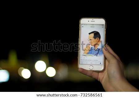 Bangkok, Thailand - October 22, 2016: Thai people show King Bhumibol Adulyadej photo on mobibe phone outside The Grand Palace.