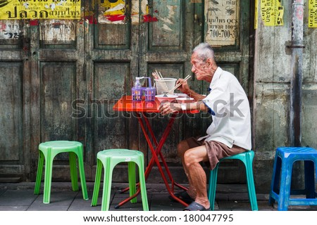 BANGKOK, THAILAND - OCTOBER 04: Unidentified man eats on a street in chinatown district, Bangkok, Thailand on October 04, 2012. Chinatown is renowned for its street food and outdoor dining. - stock photo