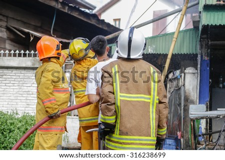 BANGKOK THAILAND-SEPTEMBER 13 : Firefighter fighting For A Fire Attack.on September 13, 2015 in Bangkhe, Bangkok, Thailand.