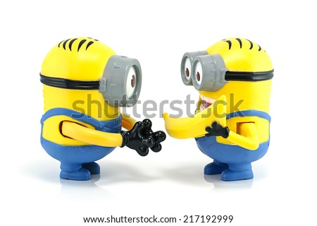 Bangkok,Thailand - September 13, 2014: Minion Dave give banana to Minion Stuart  toy character from Despicable Me 2 movie. There are plastic toy sold as part of the McDonald's Happy meals. - stock photo