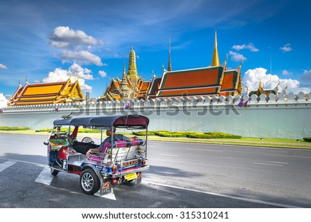BANGKOK, THAILAND - September 7: TukTuk,Taxi on road in front of the famous Buddhist Temple Wat Phra Kaew, one of the main landmarks of Bangkok, Thailand - stock photo