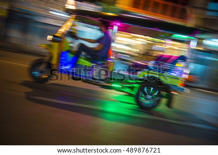 Bangkok Thailand tuk-tuk taxi zooms by in a brightly colored lights night blur