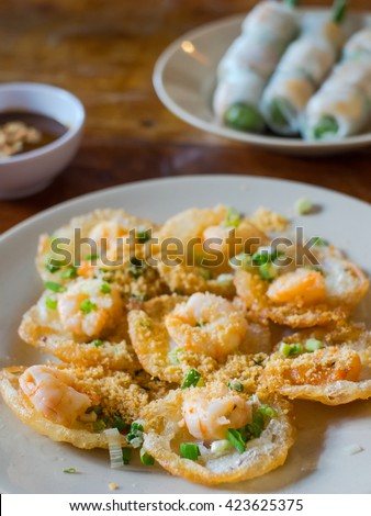 Banh Khot with shrimps, miniature fried pancakes served in Vietnam. Goi cuon, Vietnamese spring rolls, in the background. Very shallow depth of field with the first pancake in focus
