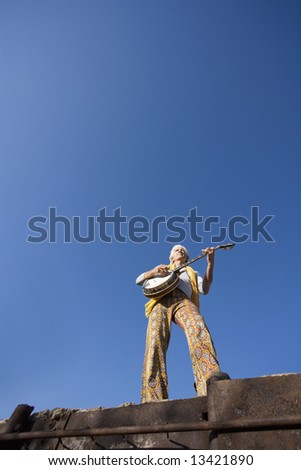 Banjo Player with groovy clothes against a wide sky