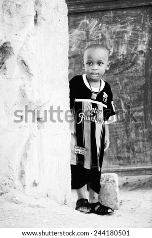 BANJUL, GAMBIA - MAR 14, 2013: Unidentified Gambian boy in FC Barcelona shirt near the house in Gambia, Mar 14, 2013. Major ethnic group in Gambia is the Mandinka - 42% - stock photo