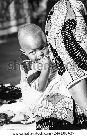 BANJUL, GAMBIA - MAR 14, 2013: Unidentified Gambian little baby boy on his mother's back in Gambia, Mar 14, 2013. Major ethnic group in Gambia is the Mandinka - 42% - stock photo