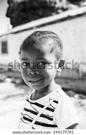 BANJUL, GAMBIA - MAR 14, 2013: Unidentified Gambian little smiling girl plays in the street in Gambia, Mar 14, 2013. Major ethnic group in Gambia is the Mandinka - 42% - stock photo