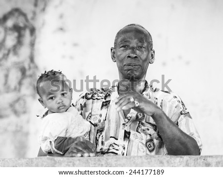 BANJUL, GAMBIA - MAR 14, 2013: Unidentified Gambian man holds her little baby child on his arms in Gambia, Mar 14, 2013. Major ethnic group in Gambia is the Mandinka - 42% - stock photo