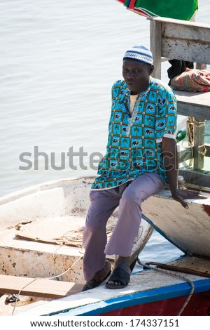 BANJUL, GAMBIA - MAR 14, 2013: Unidentified Gambian man stays on a pear in Gambia, Mar 14, 2013. People of Gambia suffer of poverty due to the unstable economical situation