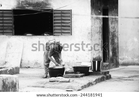 BANJUL, GAMBIA - MAR 14, 2013: Unidentified Gambian woman cleans clothes in the street in Gambia, Mar 14, 2013. Major ethnic group in Gambia is the Mandinka - 42% - stock photo