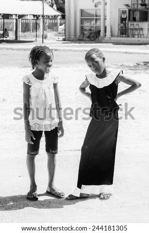 BANJUL, GAMBIA - MAR 14, 2013: Unidentified two Gambian girls stay in the street in Gambia, Mar 14, 2013. Major ethnic group in Gambia is the Mandinka - 42% - stock photo