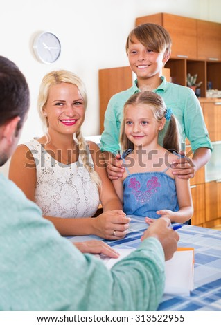 Bank agent consulting family with kids at a home interior