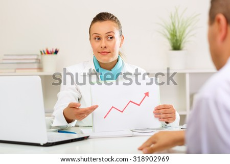 Bank clerk showing her client that the interest rates have grown. - stock photo