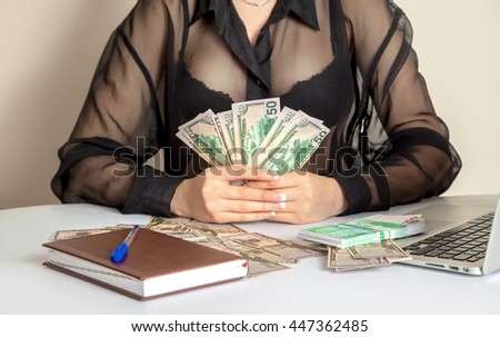 Bank employee holding a lot of money in her hands at the working table - stock photo