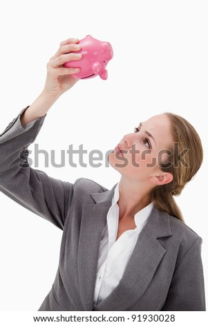 Bank employee looking at piggy bank against a white background - stock photo