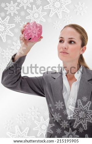 Bank employee taking close look at piggy bank against snowflakes on silver - stock photo