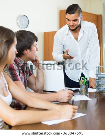 Bank employee trying hard to make young couple pay back a loan in the office