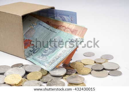 Bank notes in the box and coins  isolated on wooden table. Business concept. DOF and copy space.  - stock photo