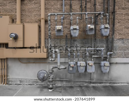 Bank of individual commercial natural gas meters on building exterior to measure  consumption  - stock photo