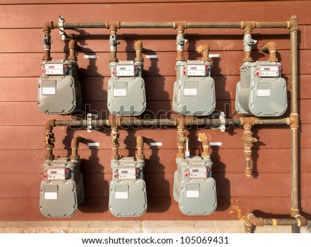 Bank of individual residential natural gas meters on building exterior to measure household consumption - stock photo