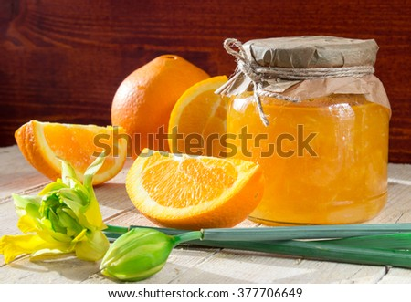 Bank of orange marmalade slices of orange and flower on a wooden background - stock photo