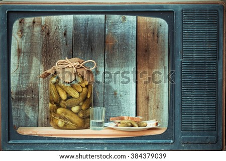 Bank of pickles, vodka and snack in the old TV, image in the soft blue toning - stock photo
