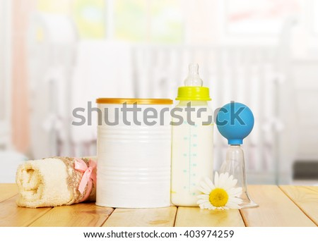 Bank of powdered milk, bottle, manual breast pump and a towel on the background of the kitchen. - stock photo