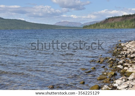 Bank of the lakes on the Putorana plateau. Summer water landscape with stones on the shore in the foreground.