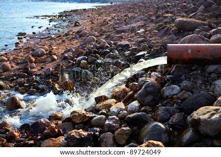 Bank of the river with large boulders and the water flows from the sewer pipe in spring day - stock photo