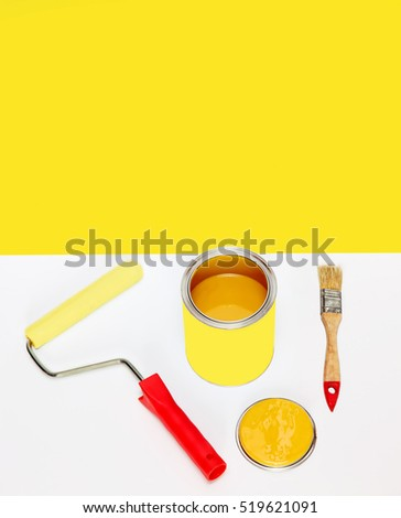 Bank of yellow paint and brushes on multicolored background with empty space for text.