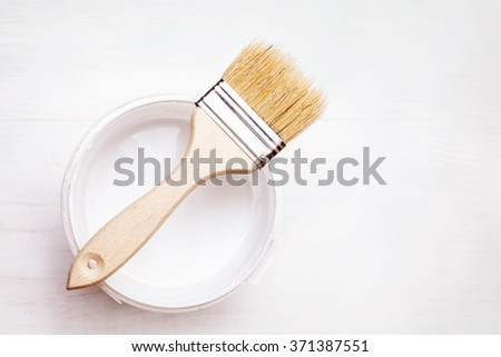 Bank paints and brush on a white wooden background - stock photo