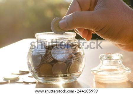 bank,piggy bank,Money,Coins,Concept, Hand saving coins money into glass piggy bank with sunset light in saving money concept - stock photo