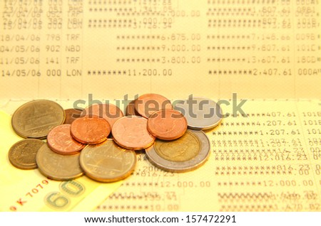Bank saving account passbook with lot of coins above - stock photo