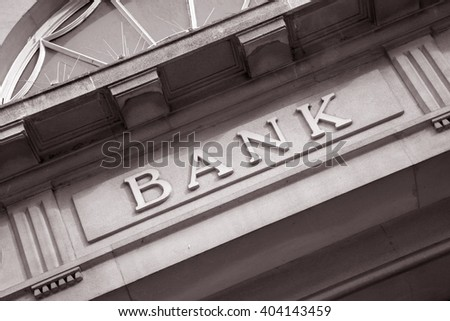 Bank Sign above Building Entrance in Black and White Sepia Tone - stock photo