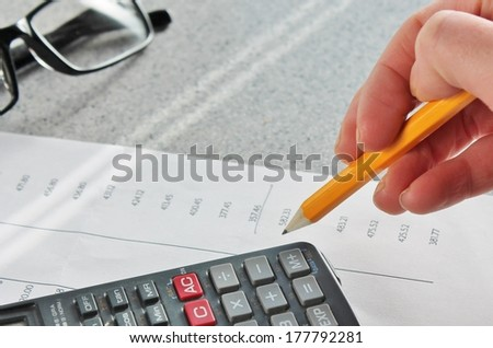Bank statement numbers with hand glasses pencil and calculator