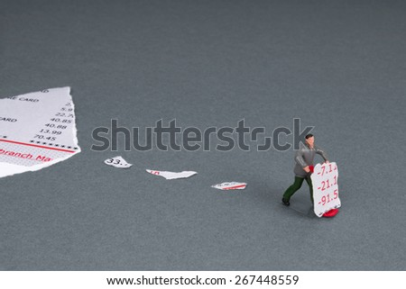 bank statement torn into little pieces and a plastic workman figurine with a torn section of bank statement on a trolley. - stock photo