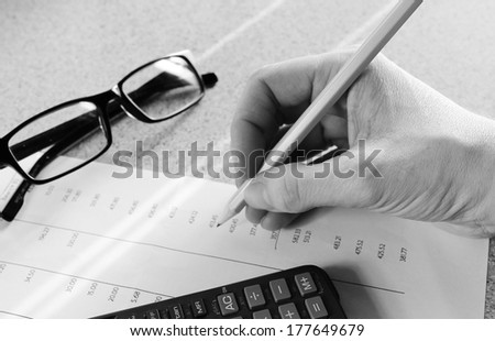 Bank statement with pencil glasses hand and calculator - stock photo