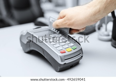 Bank terminal and a man's hand with a credit or debit card to make payments. Toned photo.