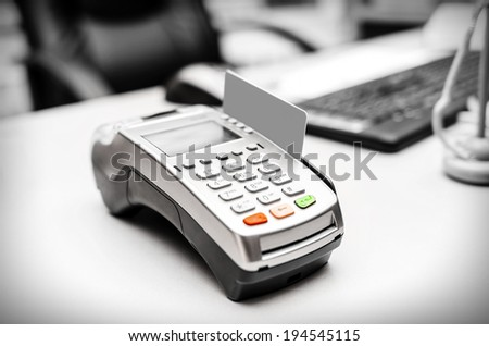 Bank terminal and payment card on the office table - stock photo