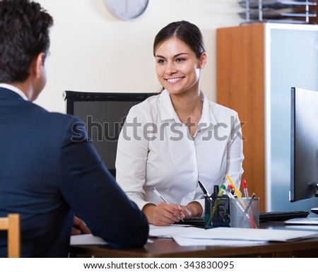 Banking agent listening to customer and smiling in agency - stock photo