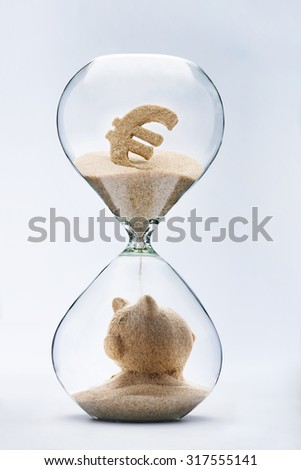 Banking concept. Piggy bank made out of falling sand from euro sign flowing through hourglass - stock photo