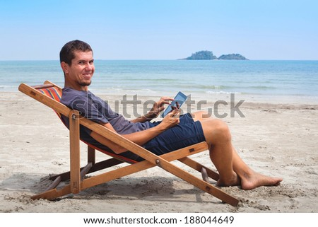 banking online, portrait of happy business man with tablet on the beach - stock photo