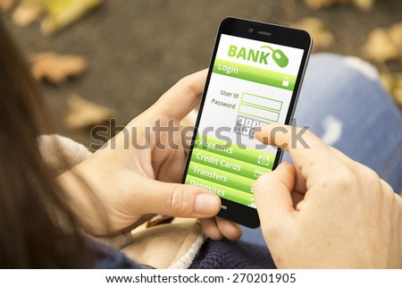 banking security concept: young woman with online banking application phone at the park - stock photo