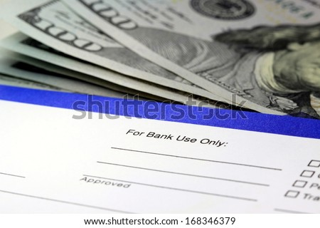 Banking withdrawal - deposit slip with US currency  - stock photo