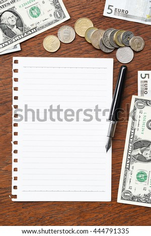 banknote and coins with notebook for background